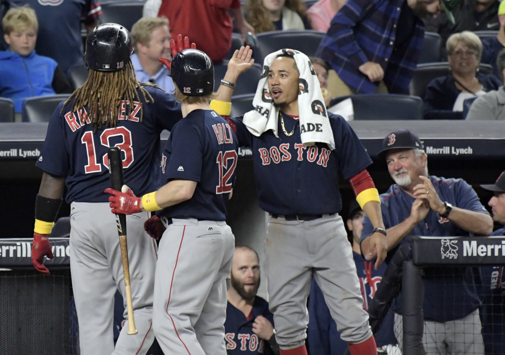 Boston's Hanley Ramirez celebrates with Brock Holt, 12, and Mookie Betts, right, after hitting a home run in the seventh inning Friday night at Yankee Stadium.