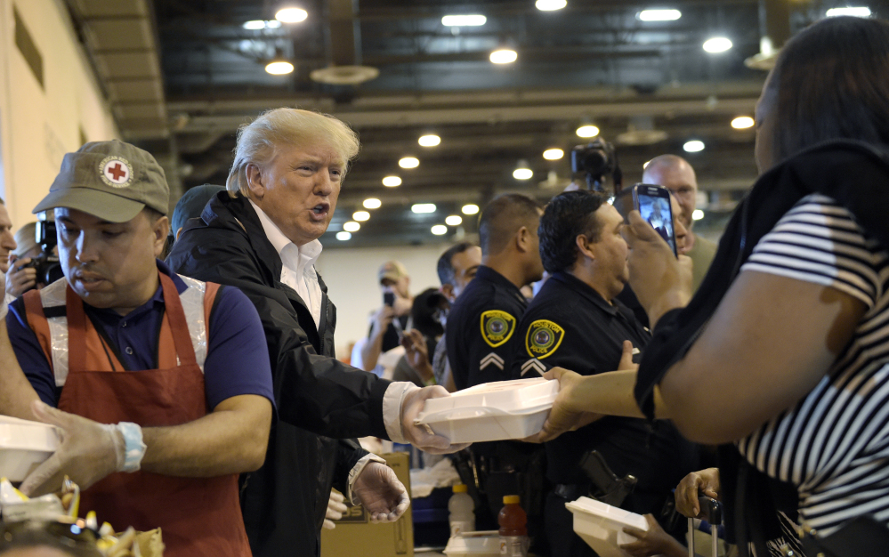 President Trump passes out food during a visit to the NRG Center in Houston, Texas, on Saturday. It was his second trip to Texas in a week, and this time his first order of business was to meet with those affected by Hurricane Harvey.