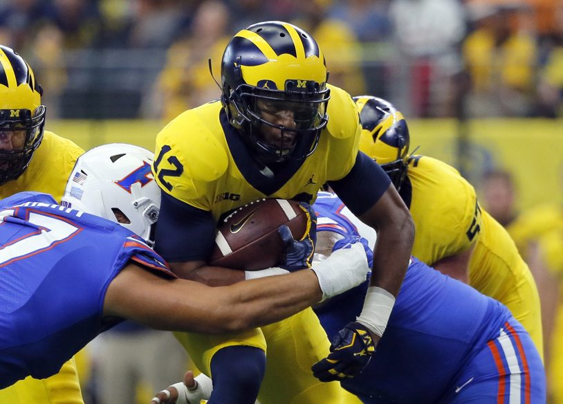 Florida defensive lineman Jordan Sherit, left, attempts to stop Michigan running back Chris Evans with help from teammates during their season opener Saturday in Arlington, Texas. No. 11 Michigan beat No. 17 Florida, 33-17.