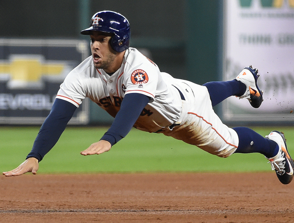 Houston's George Springer slides safely into third on Alex Bregman's single during the Astros' 12-8 win in Game 1 of a doubleheader against New York on Saturday.