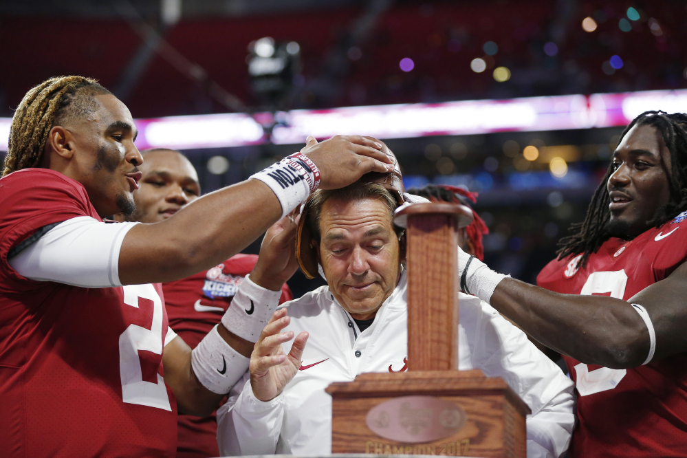 Alabama quarterback Jalen Hurts, left, and running back Bo Scarbrough place the Leather Helmet trophy on coach Nick Saban's head. Alabama won 24-7