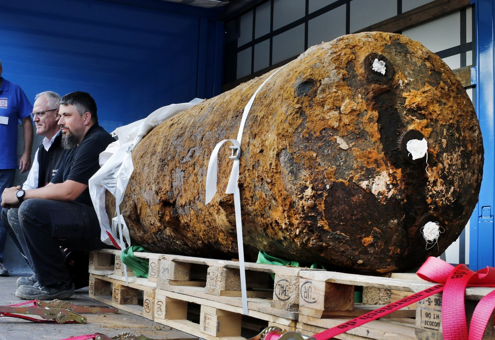 Bomb disposal experts Dieter Schwaetzler, left, and Rene Bennert sit next to a 1.8-ton World War II-era  bomb after they defused it in the German financial capital of Frankfurt on Sunday. More than 60,000 people had to be evacuated. Associated Press/Michael Probst