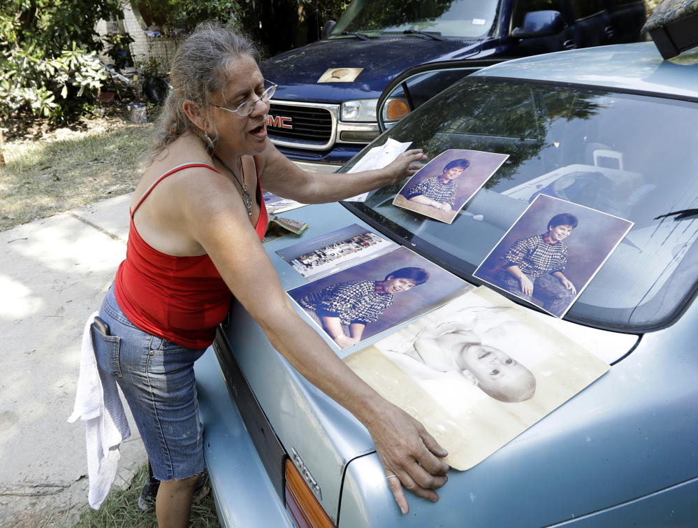 Pam Murray places a damaged baby picture of her son, Rob, on a trunk of a car to dry out Sunday while cleaning out her mother's home, which was destroyed by floodwaters in the aftermath of the Category 4 Hurricane Harvey in Spring, Texas.