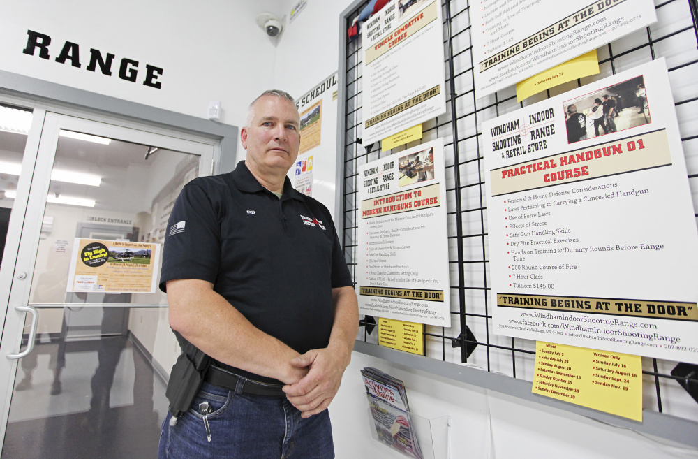 Bill Keith stands by a board with practical handgun course information. Bill Keith is a shooting instructor at Windham Indoor Shooting Range. Staff photo by Jill Brady