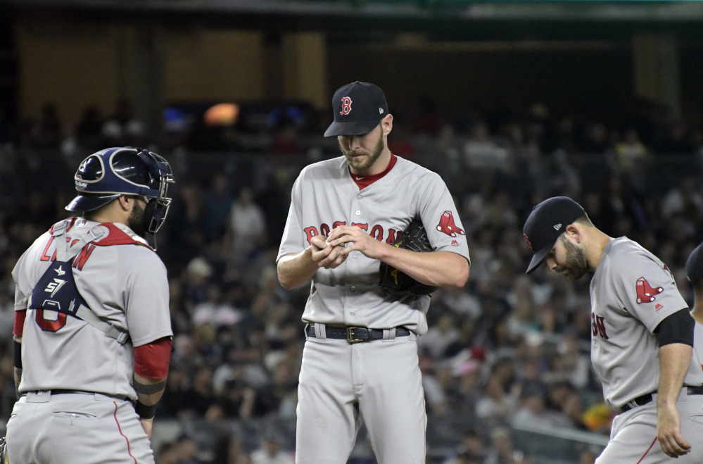 Boston Red Sox pitcher Chris Sale, catcher Sandy Leon, left, and second baseman Dustin Pedroia gather on the mound during the fourth inning of Sunday night's game against the New York Yankees in New York. (AP Photo/Bill Kostroun)
