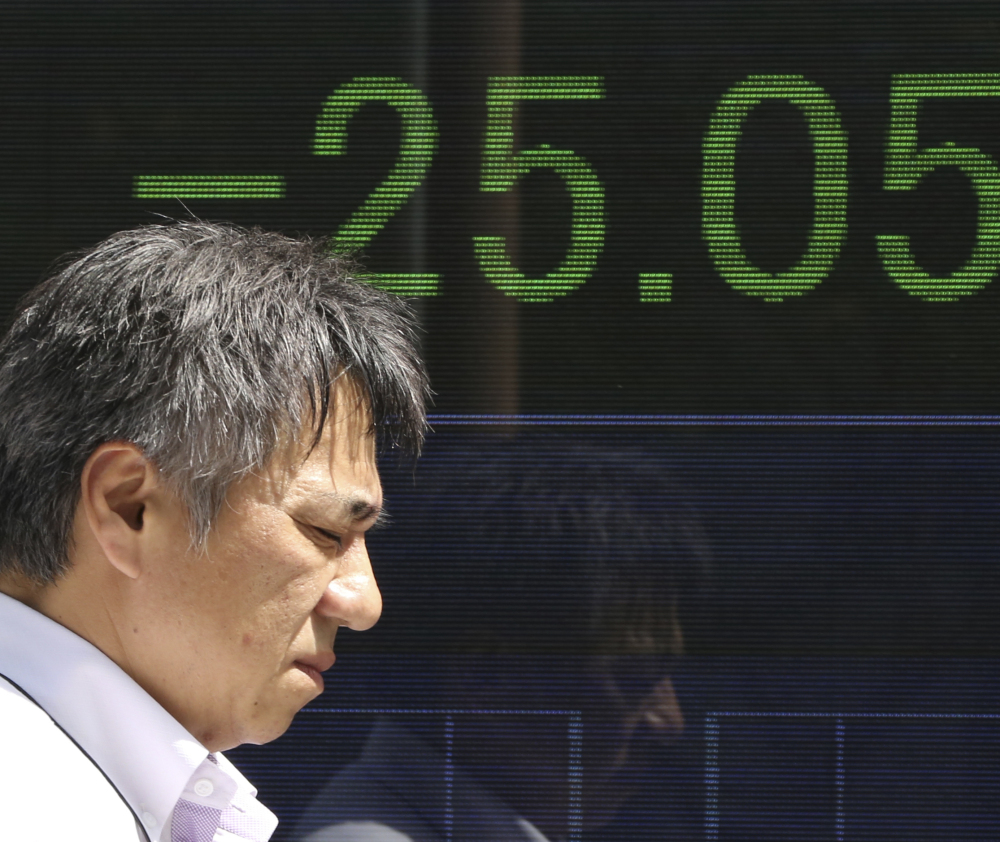 A man walks by an electronic stock board of a securities firm in Tokyo. Asian shares including Japan's Nikkei index were mostly lower Monday, following the news that North Korea said it successfully tested a hydrogen bomb.
