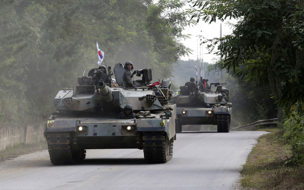 """South Korean tanks move during a military exercise Monday in Paju, South Korea, near the border with North Korea. Following U.S. warnings to North Korea of a """"massive military response,"""" South Korea's military fired missiles into the sea Monday to simulate an attack on the North's main nuclear test site."""