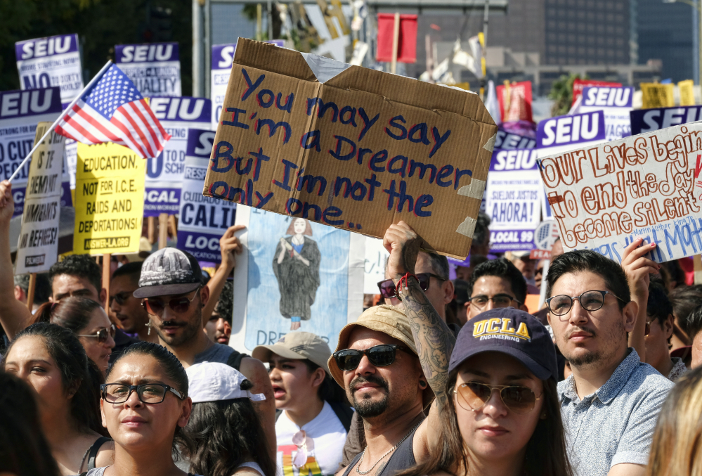 Above and below, young and older supporters of the Deferred Action for Childhood Arrivals, or DACA, program chant slogans and hold signs while joining a Labor Day rally Monday in downtown Los Angeles.