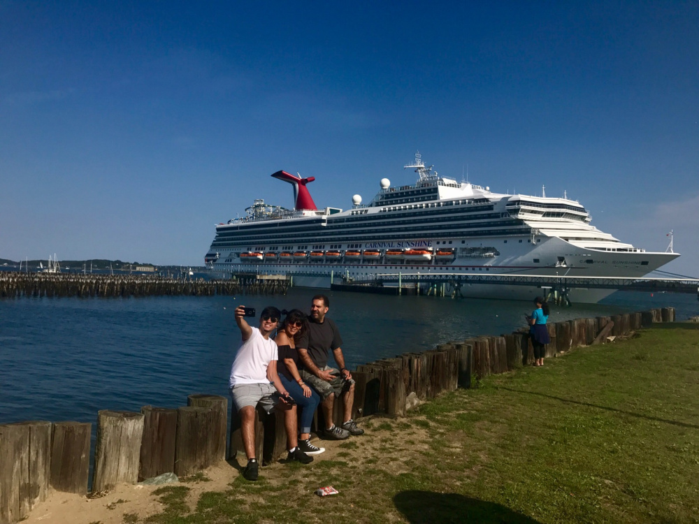 The Estrella family of New York City takes a selfie Monday with the Carnival Sunshine berthed on Portland's waterfront. Ethan Estrella, left, and his parents, Monica and Biro Estrella, who were not passengers on the ship, were in Portland after a trip farther north for a seafood festival. The Carnival Sunshine was one of two big cruise ships in Portland Harbor over the Labor Day weekend as the busiest part of the cruise ship season gets underway.
