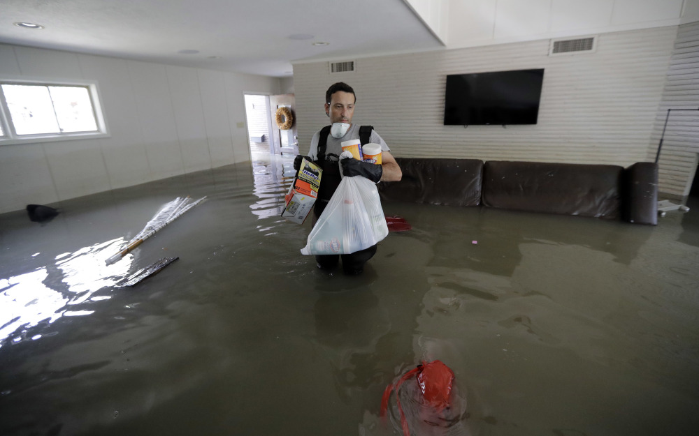 Gaston Kirby walks through floodwater still in his home in Houston on Monday, 10 days after Harvey hit.
