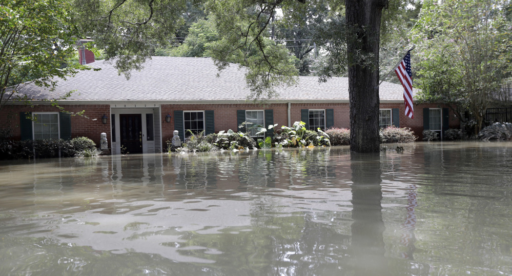A flag hangs outside a flooded home Monday near the Addicks and Barker Reservoirs in Houston. The historic storm inundated exclusive neighborhoods as well as low-lying apartments for the poor.