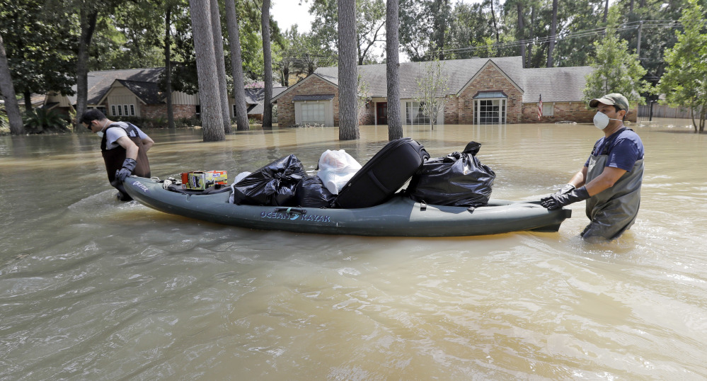 Gaston Kirby, left, is helped by his friend Juan Minutella on Monday after gathering the last of his belongings from his flooded home in the aftermath of Harvey.