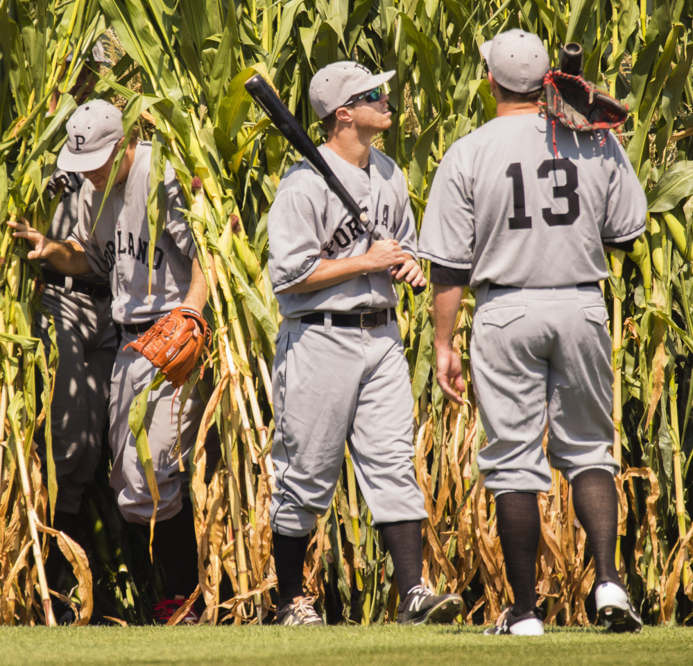 It's not heaven, or Iowa, but Hadlock Field that Portland Sea Dogs players Ty Buttrey, left, Mike Myers and Danny Bethea emerge onto from the cornfield in center field for the team's annual Field of Dreams game on Monday.