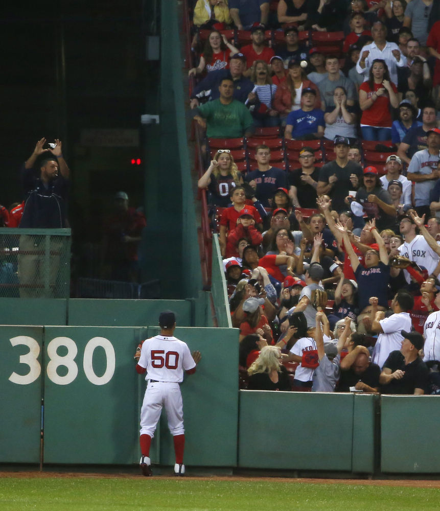 Mookie Betts watches a three-run home run ball hit by the Blue Jays' Kendrys Morales in the first inning.