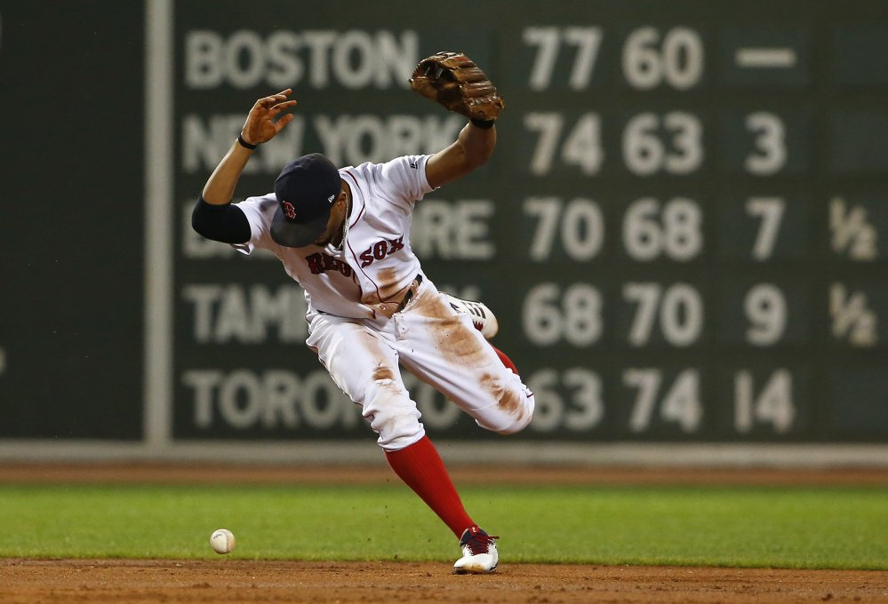 Red Sox shortstop Xander Bogaerts loses the ball while trying to force out a runner at second base in the second inning of Monday night's game – and ugly game for Boston.