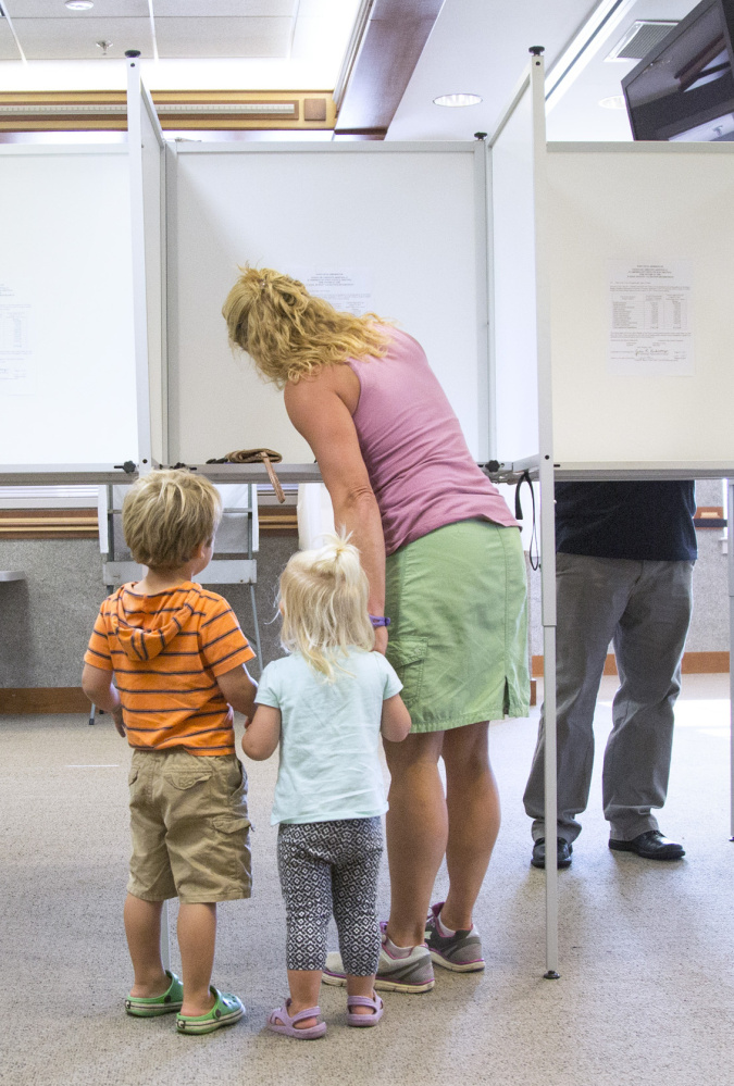 Scarborough resident Kelly Pietrzak casts her vote on the school budget with her children Marek, 3, left, and Kaja, 2, at the town hall on Tuesday.