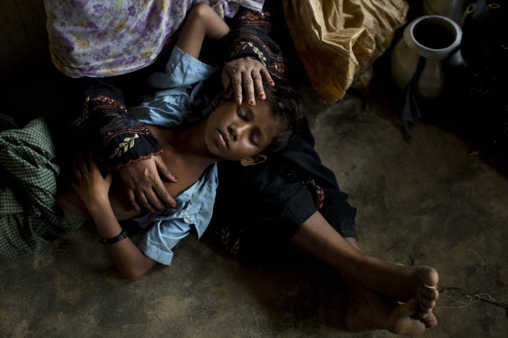 A Rohingya woman comforts her exhausted son as they take shelter at a refugee camp in Bangladesh after having just arrived from the Myanmar side of the border Thursday.