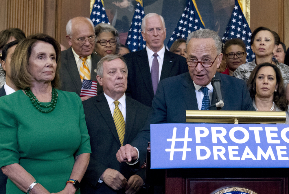 Senate Minority Leader Chuck Schumer of New York and House Minority Leader Nancy Pelosi of California appear with Democrats on Wednesday in Washington. President Trump's alliance with Democrats has Republicans baffled.
