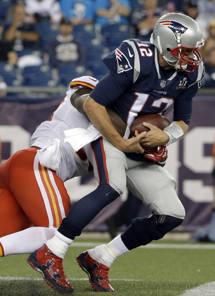 Kansas City Chiefs linebacker Justin Houston, left, sacks Patriots quarterback Tom Brady during the second half of New England's 42-27 loss at home Thursday night.