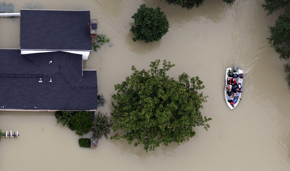 Residents evacuate their homes near the Addicks Reservoir as floodwaters from Tropical Storm Harvey rise in Houston on Aug. 29. Heavily subsidized federal flood insurance has tilted migration toward vulnerable coastal regions of the Sunbelt.