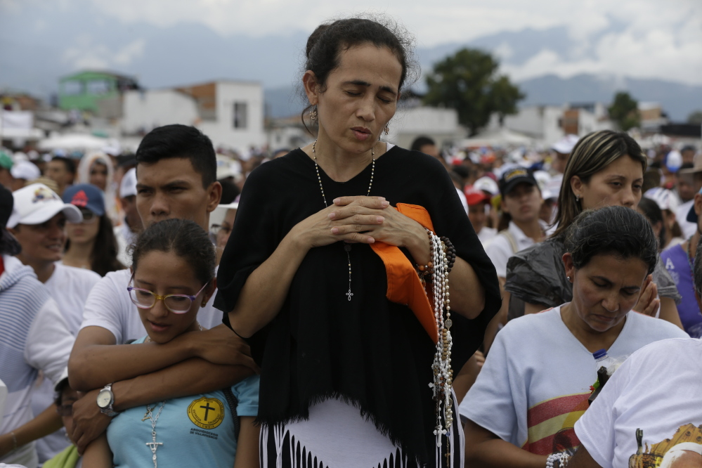 A woman prays during a Mass celebrated by Pope Francis in Villavicencio, Colombia, on Friday, as he continues a five-day trip to that country. Associated Press/Ricardo Mazalan