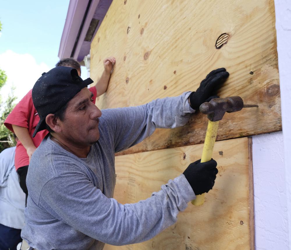 As Irma closes in, Pedro Reimundo nails plywood shielding on a home in Florida City, Fla., on Friday.