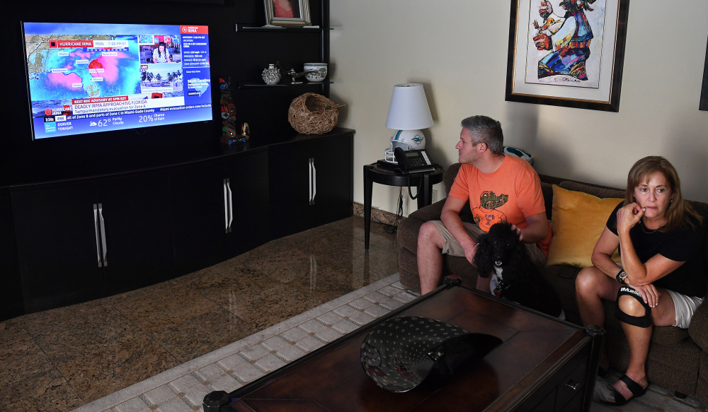 Adam Fischer watches coverage of Hurricane Irma on Friday at the home of his mother-in-law, Jan Bell Pollack, less than a mile from Biscayne Bay. The Pollacks – including Penny the poodle – plan to ride out the storm at home.