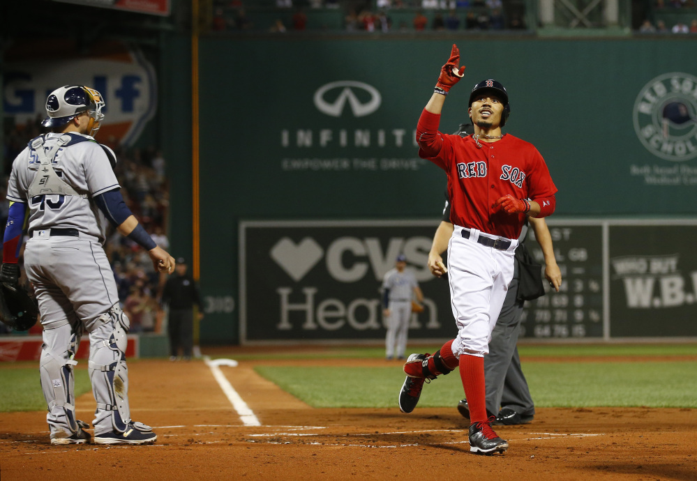 Mookie Betts points skyward after hitting a three-run home run as Tampa Bay Rays catcher Jesus Sucre watches in the first inning Friday night at Fenway Park.