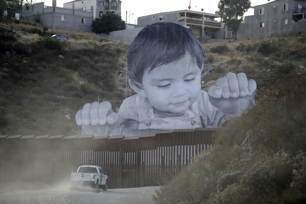 A 65-foot-tall photo of a Mexican boy, mounted on scaffolding in Tecate, Mexico, appears to look over a section of border wall on the California border Friday.