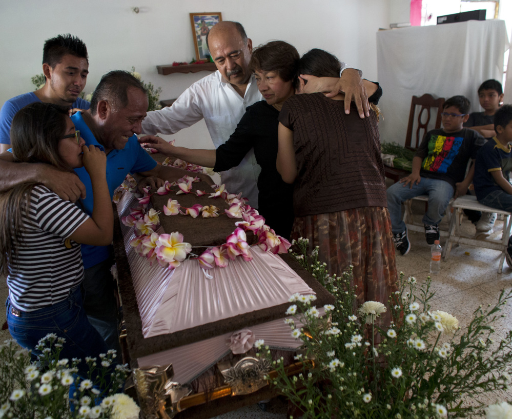 Family members grieve over the coffin containing the remains of 64-year-old Reynalda Matus Martinez during a wake in Juchitan, Oaxaca state, Mexico, on Saturday.