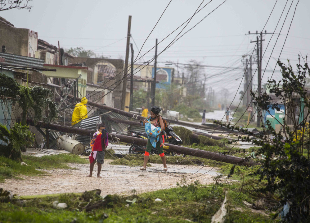 Residents walk near downed power lines felled by Hurricane Irma in Caibarien, Cuba, on Saturday. There were no reports of deaths or injuries after heavy rain and winds from Irma lashed northeastern Cuba.