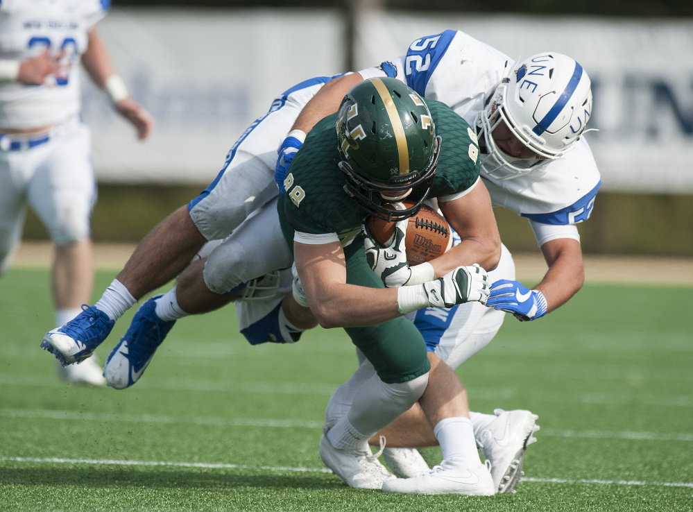 University of New England linebacker Nick Scarfo brings down Patrick Cullen during Sunday's game against Husson University's JV team in Bangor. UNE, which is playing JV and prep school opponents this fall before moving to varsity status in 2018, lost 34-21.