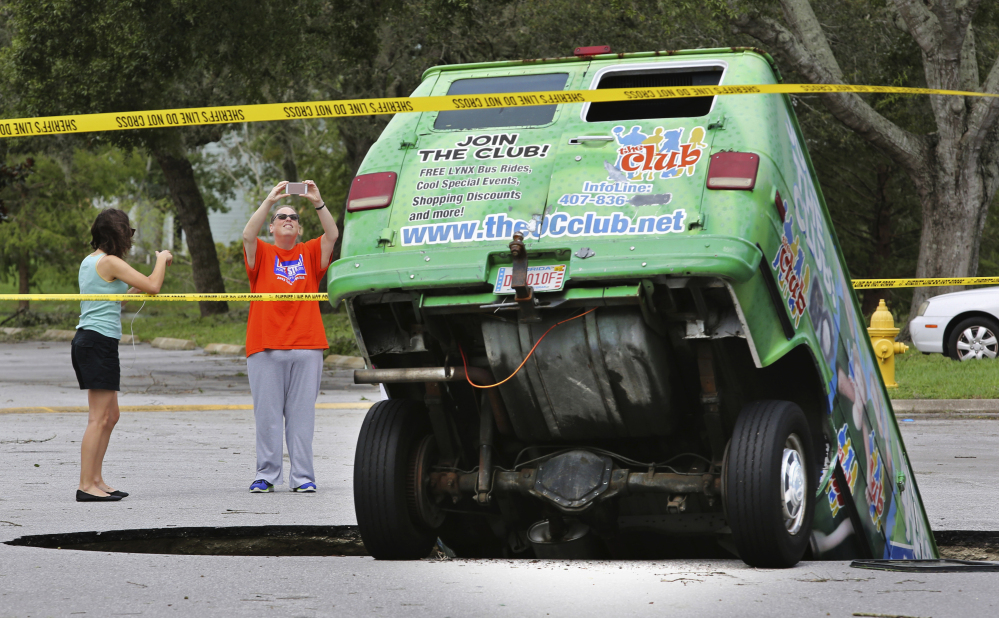 Residents on Monday take photos of a van in a sinkhole that opened up at the Astor Park apartment complex in Winter Springs, Fla., during Hurricane Irma's passing through central Florida.