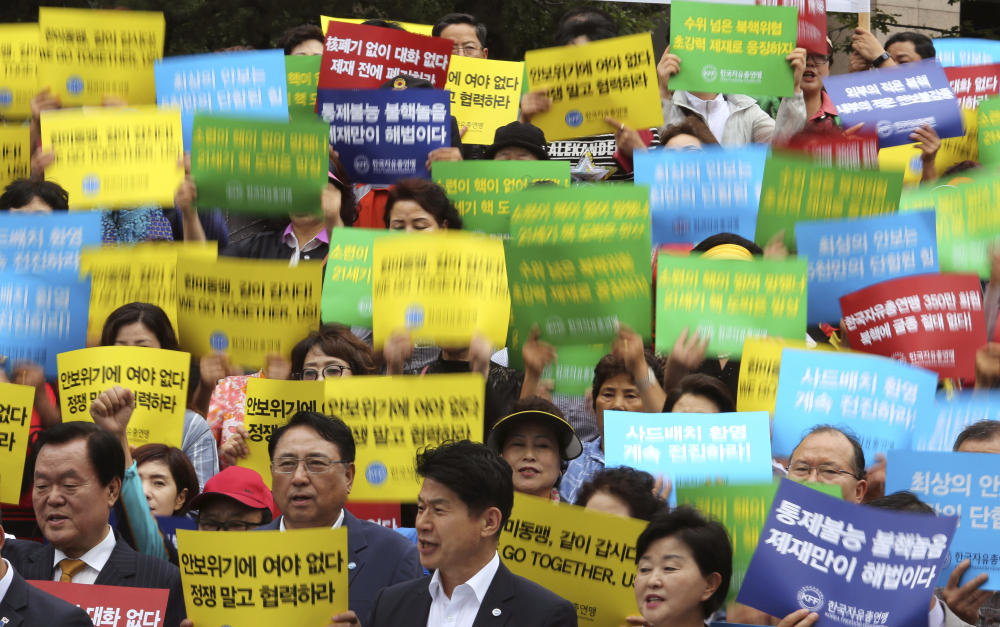 Members of the Korea Freedom Federation shout slogans during a rally to denounce North Korea's latest nuclear test in Seoul, South Korea, on Monday. North Korea threatened to make the U.S. pay a heavy price in retaliation for tough new sanctions on Pyongyang.