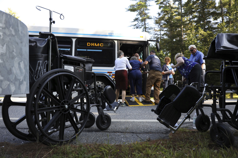First responders and Dartmouth Hitchock Medical Center staff help a patient onto an evacuating bus after an active shooter was reported Tuesday at the medical center in Lebanon, N.H. A family member shot and killed a 70-year-old female patient in the Intensive Care Unit, police say.