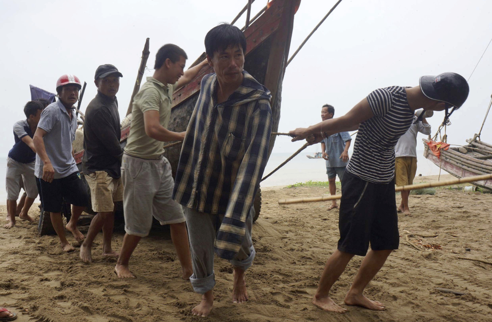 Vietnamese villagers move a fishing boat on shore in northern Thanh Hoa province Thursday, ahead of Typhoon Doksuri, which killed four people and injured 10 others.
