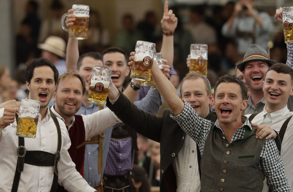 Young men celebrate the opening of the 184th Oktoberfest beer festival in Munich, Germany, on Saturday.