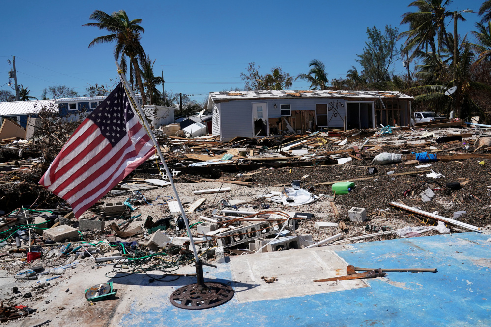 "A flag flies over a debris field of destroyed houses following Hurricane Irma in Islamorada, Fla., on Friday. Returning residents of the Keys were told electricity, sewer and water were ""intermittent at best."" Curfews are in effect and schools are still closed until at least Sept. 28."