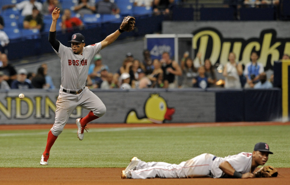 Boston's Xander Bogaerts, left, and Rafael Devers cannot stop a ground ball single hit by Tampa Bay's Evan Longoria that drove in Jesus Sucre from third base during the fifth inning of the Red Sox' 3-2 loss Sunday in St. Petersburg, Florida.