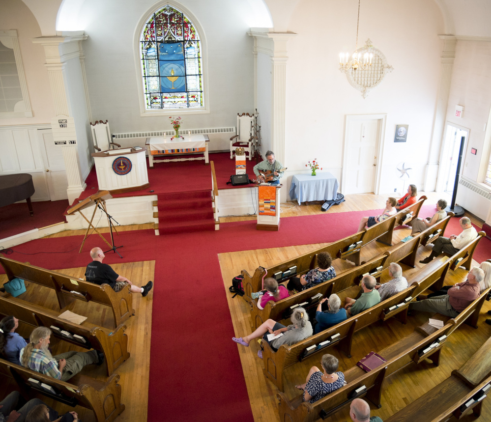 The congregation at the Universalist Unitarian Church in Waterville listens as Stan Davis plays his guitar and sings during a service Sunday.
