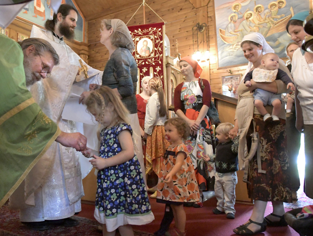 Nathan Williams, second from left, is greeted Sunday by his mother, Cindy, after his elevation to the priesthood in the Russian Orthodox Church during services at the St. Alexander Nevsky Church in Richmond.