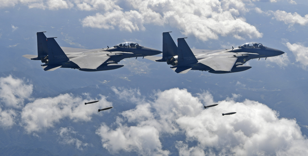 In this photo provided by South Korea Defense Ministry, South Korean F-15K fighter jets drop bombs as they fly over the Korean Peninsula during joint drills with the U.S.