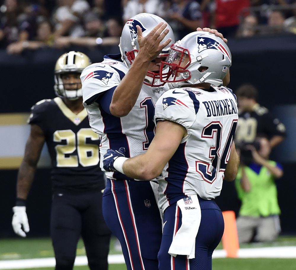 New England Patriots running back Rex Burkhead (34) celebrates his touchdown with quarterback Tom Brady in the first half Sunday against the Saints.