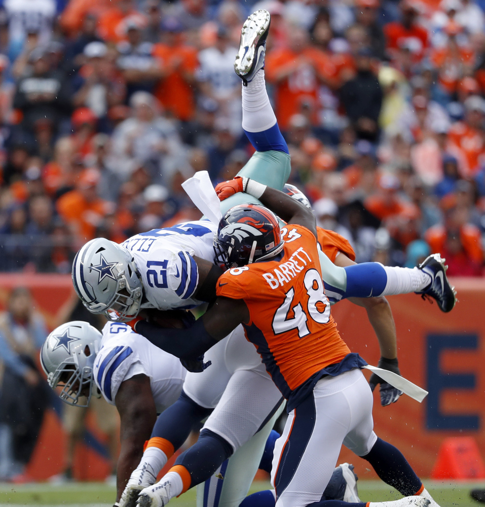 Dallas Cowboys running back Ezekiel Elliott, top, is hit by Denver outside linebacker Shaquil Barrett during the Broncos' 42-17 win Sunday. Elliott was held to 8 yards on nine carries.