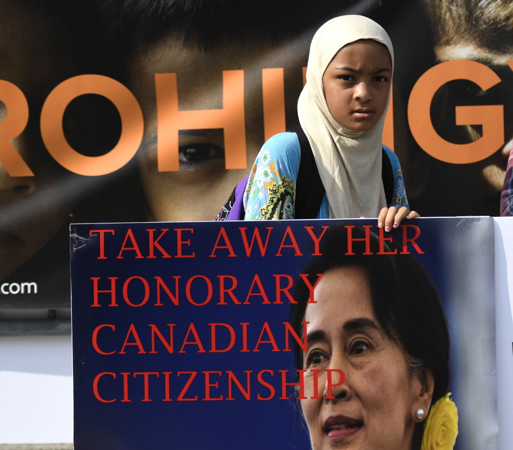 A girl holds a sign calling for the removal of the honorary Canadian citizenship of Myanmar leader Aung San Suu Kyi, during a rally in Ottawa on Sunday.