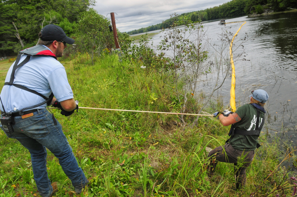 After somebody on a boat tossed it to them, Tim House, a trainer from Moran Environmental Recovery, left, and Tiffany LaClair, of the Department of Environmental Protection, pull the rope on a containment boom onto shore Tuesday during a training exercise in the Kennebec River off Swan Island.