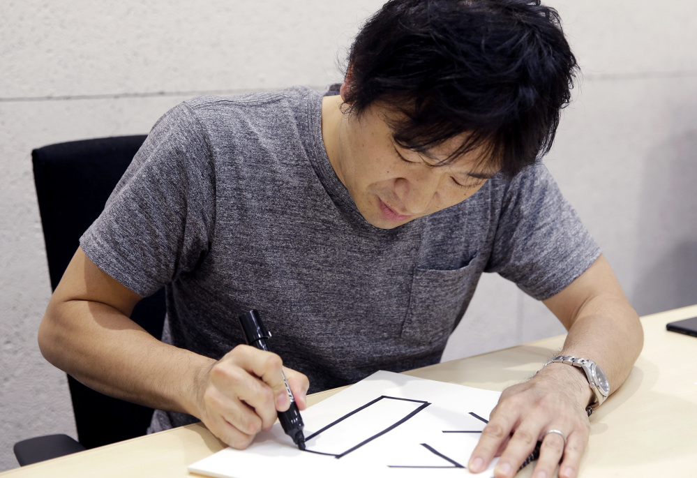 Django Co., Ltd. Director Shigetaka Kurita writes a pictograph during an interview at his office in Tokyo.