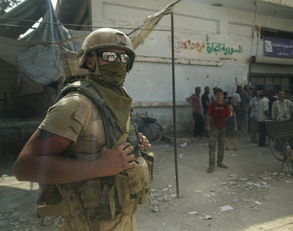 A Russian soldier guards a city market in Deir al-Zour, Syria. A U.S.-backed force in Syria said a Russian airstrike wounded six of its fighters Saturday near Deir al-Zour. Associated Press