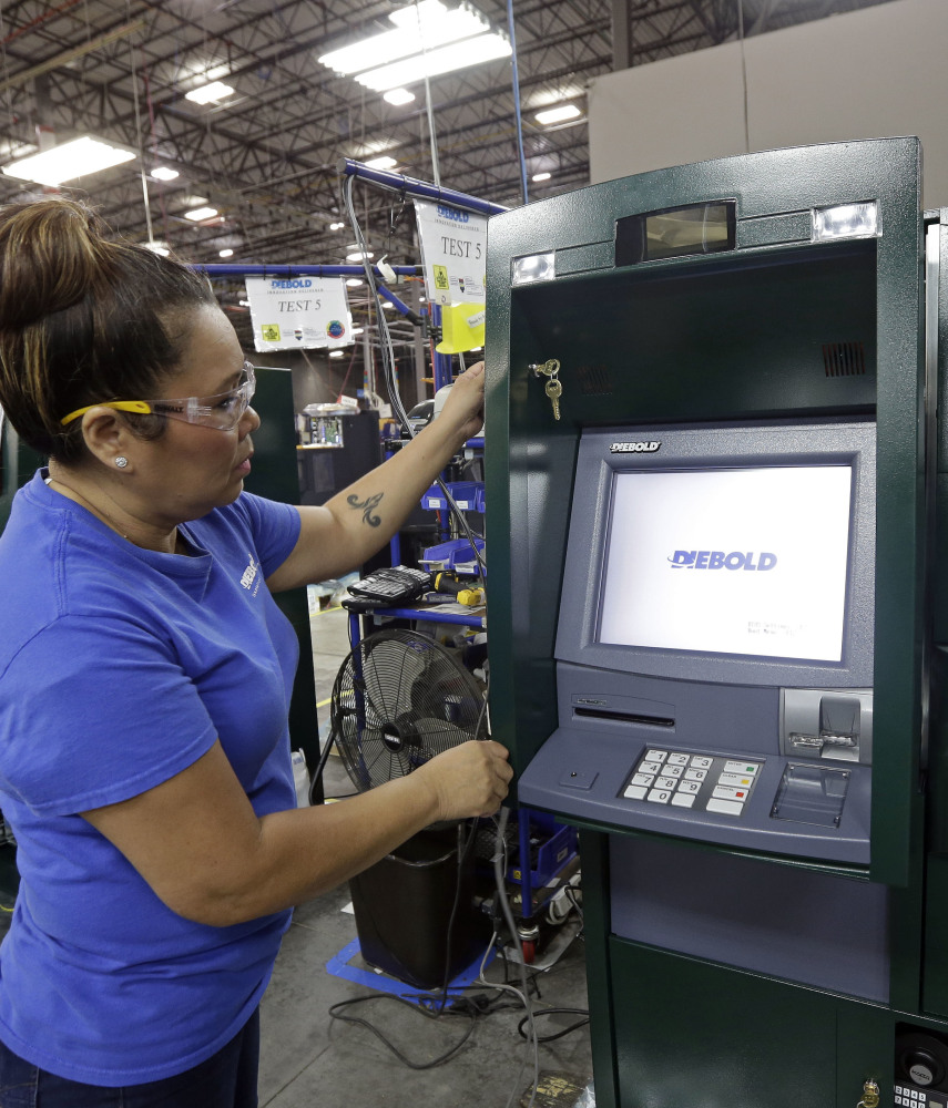 A Diebold Nixdorf worker installs software in a new version of ATMs, some of which act more like smart devices with swiping and other features.