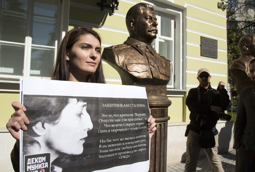 A woman protests the unveiling of Josef Stalin's bust in Moscow. The poster carries the verses of poet Anna Akhmatova denouncing those who try to whitewash Stalin.